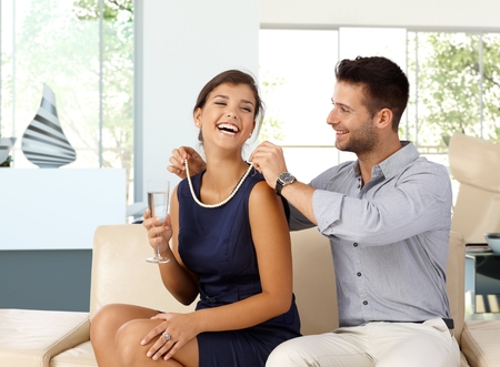 Photo pour Happy caucasian woman with champagne in hand getting pearl necklace gift from husband. Happy couple, sitting at home on sofa in living room, romance, jewelry. - image libre de droit