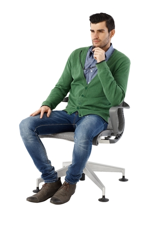 Photo pour Handsome young businessman sitting and thinking in swivel chair over white background, looking away. Full size. - image libre de droit
