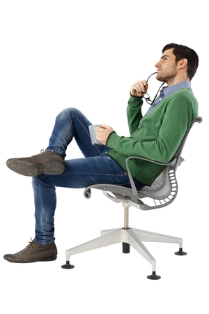 Photo pour Side view of daydreaming young man sitting in swivel chair - image libre de droit