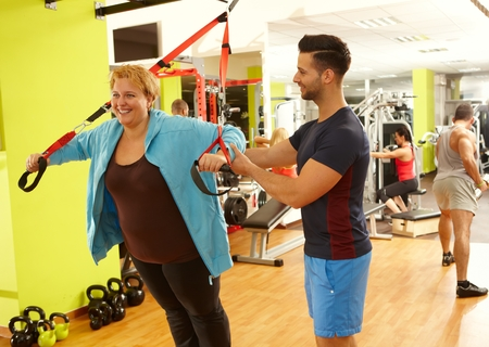 Photo pour Overweight woman doing suspension training with the guidance of personal trainer. - image libre de droit