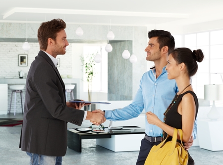 Photo pour Young couple and real estate agent shaking hands, smiling. Side view. - image libre de droit