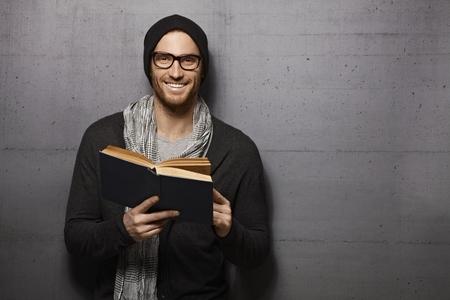 Foto de Happy urban style young man standing against grey wall, smiling, reading book, looking at camera. - Imagen libre de derechos