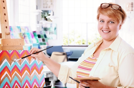 Photo pour Happy fat woman painting at home, smiling, looking at camera. - image libre de droit