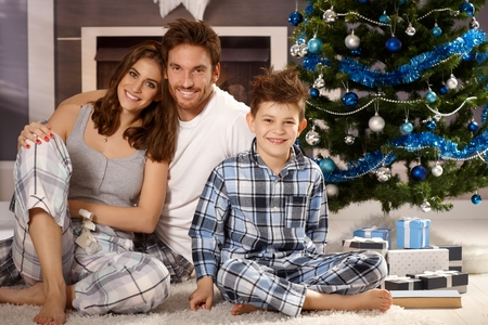 Happy young family sitting on floor at christmas morning in pajamas, smiling, looking at camera.