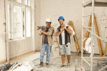 Photo pour Happy workers standing at renovation site, smiling, looking at camera. - image libre de droit