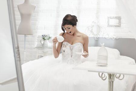 Foto de Unlucky bride spilling coffee on wedding dress, looking shocked. - Imagen libre de derechos