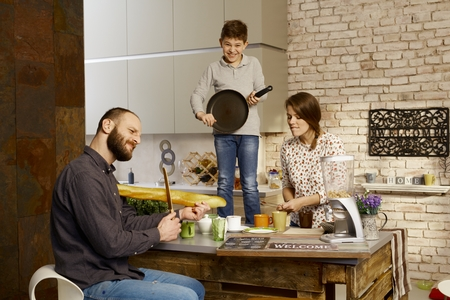 Photo pour Family forming a band in kitchen, pretending to play on instruments. - image libre de droit