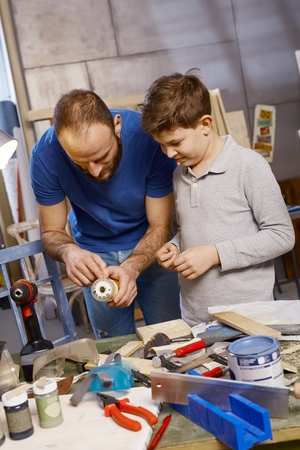 Father and son tinkering in workshop.