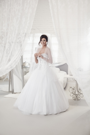Photo pour Beautiful bride standing in bedroom in wedding dress, smiling happy. Full size. - image libre de droit