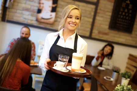 Foto de Happy blonde waitress holding tray, working in cafeteria. - Imagen libre de derechos