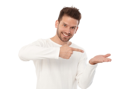 Photo for Happy young man pretending to hold something in left hand, pointing to it by other hand. - Royalty Free Image