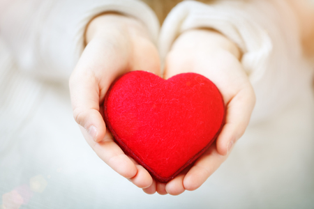 Foto de Red heart in hands of the little girl. Symbol of love and family.Valentines day card. Mothers day. Backgrounds for social posters. Selective focus. - Imagen libre de derechos