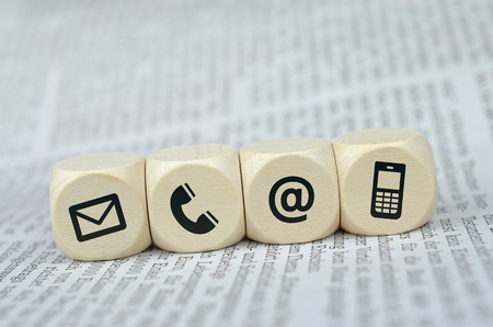 Photo pour Website and Internet contact us page concept with black icons on cubes on a newspaper - image libre de droit