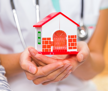 Photo pour Photo of miniature house holding in young doctor hands - image libre de droit
