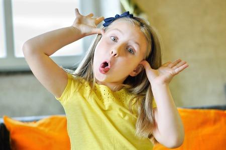 Foto de Little adorable girl making funny face and showing her tongue - Imagen libre de derechos