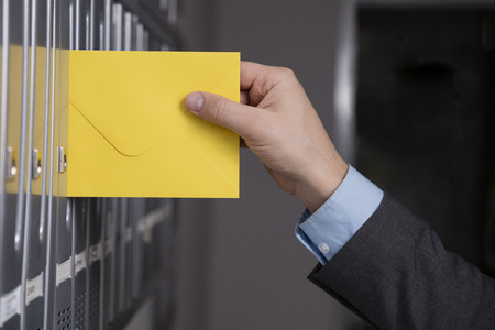 Foto de Mailman's hand putting the yellow envelope into the gray mailbox - Imagen libre de derechos