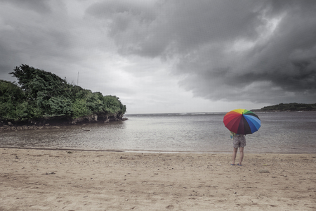 A lady and colorful umbrella at the beach with stormy sky