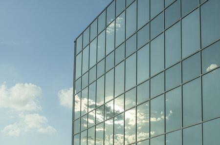 Foto de Office building windows with white clouds and shining sun in a blue sky - Imagen libre de derechos