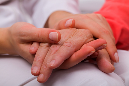 Foto per Caregiver holding elderly patients hand at home - Immagine Royalty Free