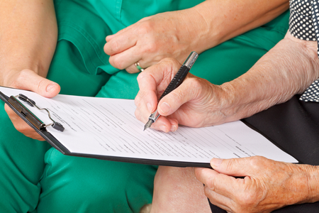 Photo pour A senior woman's hand signing a document - image libre de droit