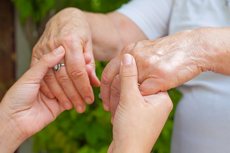 Foto de Close up young caregiver holding elderly female's trembling hands, Parkinson disease - Imagen libre de derechos