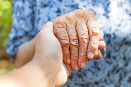Photo for Close up elderly female's shaking hand held by young carer's hands outdoor - Royalty Free Image