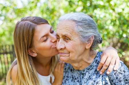 Photo pour Young woman kissing her old grandmother in the park - image libre de droit