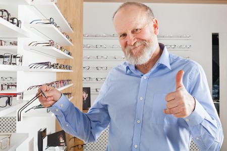 Foto de Cheerful elderly man choosing corrective glasses in optics store - Imagen libre de derechos
