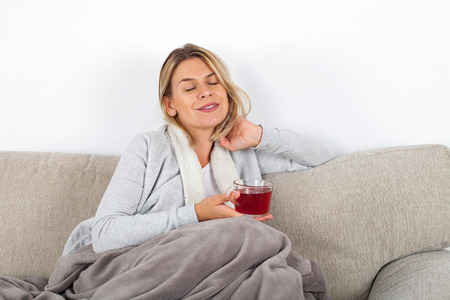 Photo for Beautiful woman relaxing on the sofa and drinking hot tea, wrapped in a grey blanket - Royalty Free Image