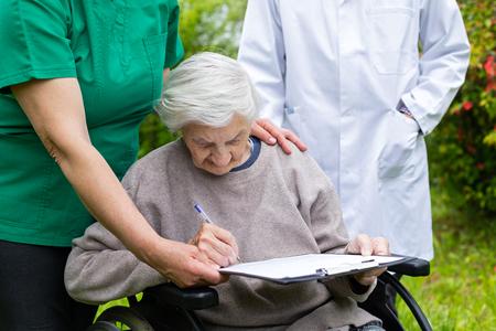 Photo pour Close up picture of invalid elderly woman signing insurance form at the nursing home - image libre de droit