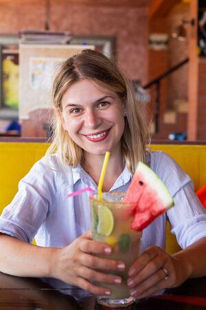 Foto de Woman holding a cold refreshing  lemonade at a beach terrace on a hot summer day - Imagen libre de derechos