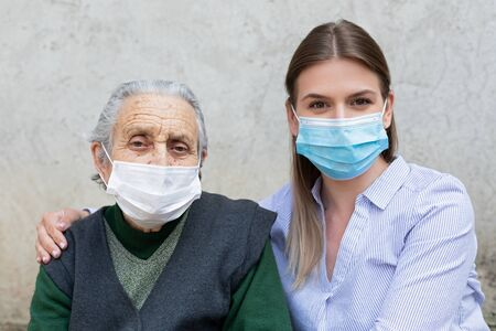 Photo pour Portrait of friendly caregiver posing with elderly ill woman wearing surgical mask because of covid-19 pandemic - image libre de droit