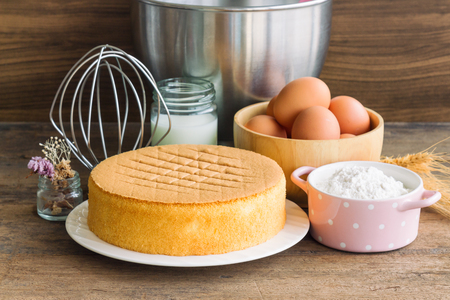 Photo for Homemade sponge cake on white plate.Soft and lite delicious sponge cake with ingredients: eggs flour milk on wood table. Homemade cake with ingredients in homemade bakery concept for bakery background - Royalty Free Image