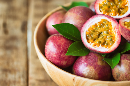 Photo for Close up fresh passion fruit in wood bowl on wood table in side view with copy space for background or wallpaper. Ripe passion fruit so delicious sweet and sour. Tropical fruit. Macro concept. - Royalty Free Image