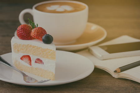 Foto de Homemade delicious and soft strawberry shortcake on wood table beside smartphone and hot cappuccino coffee at bakery shop or cafe restaurant. Vanilla sponge cake with whipped cream and strawberries. - Imagen libre de derechos