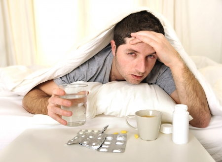Foto de exhausted young Man in bed with coffee, water and tablets suffering hangover and headache - Imagen libre de derechos