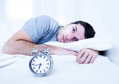 Foto de young man in bed with eyes opened suffering insomnia and sleep disorder thinking about his problem - Imagen libre de derechos