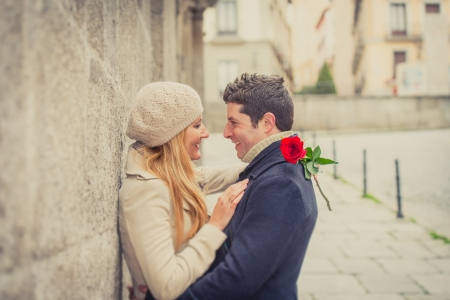 Photo pour young man giving his girlfriend a rose and kissing celebrating valentines day  - image libre de droit