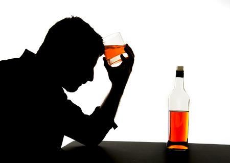 Foto de silhouette of alcoholic drunk man drinking whiskey bottle feeling depressed falling into addiction problem - Imagen libre de derechos