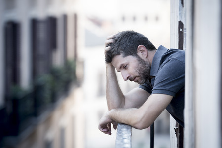 young man alone outside at house balcony terrace looking depressed, destroyed, wasted and sad suffering emotional crisis and depression