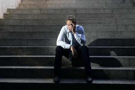 Foto de Young business man crying abandoned lost in depression sitting on ground street concrete stairs suffering emotional pain, sadness, looking sick in grunge lighting - Imagen libre de derechos
