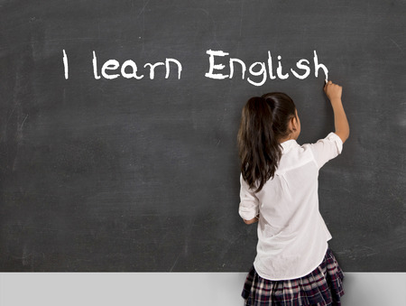 Foto de sweet little Hispanic girl at school lesson with ponytail and uniform writing with chalk on classroom blackboard in English learning , wisdom and successful education concept - Imagen libre de derechos