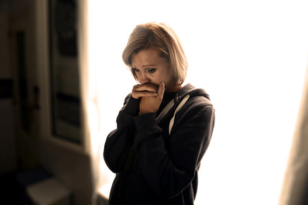Foto de young attractive woman suffering depression and stress standing alone crying in pain and grief against window feeling sad and desperate at home with studio backlight - Imagen libre de derechos