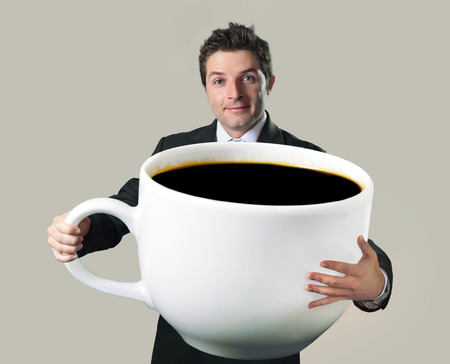 Foto de young happy business man holding a funny huge and oversized cup of black coffee in caffeine addiction concept isolated on even background - Imagen libre de derechos