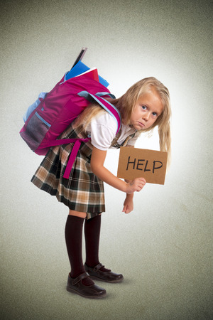 Photo for young blonde schoolgirl holding help sign carrying heavy backpack or school bag full causing stress and pain on back due to overweight isolated on grunge  background - Royalty Free Image