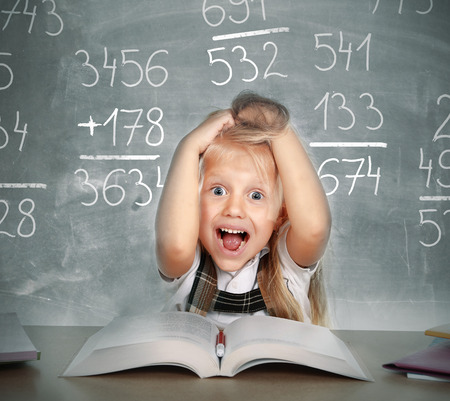 Photo for sweet little school girl pulling her blonde hair in stress getting crazy with maths calculation studying doing homework in children education concept on blackboard full of numbers - Royalty Free Image