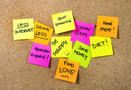Photo for Group of New year Resolutions Post it Notes on pink, yellow, orange and green on cork board written with message of diet, join gym, find love, quit smoking and be happy - Royalty Free Image