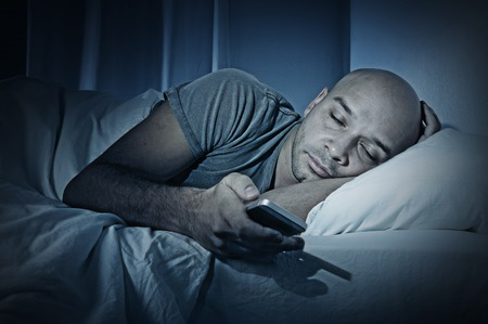 Photo pour young cell phone addict man sleeping at night in bed while using smartphone for chatting, flirting and sending text message  in internet addiction and mobile abuse concept - image libre de droit