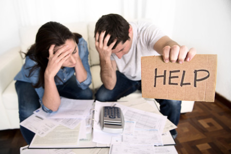 Foto de young couple worried need help in stress at home couch accounting debt bills bank papers expenses and payments feeling desperate in bad financial situation - Imagen libre de derechos