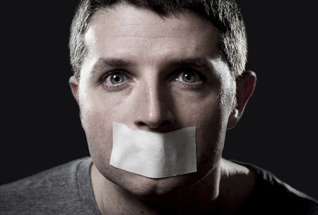 Photo pour attractive young man with mouth and lips sealed on tape to prevent from speaking free keeping him mute and censored in freedom of speech and expression concept - image libre de droit